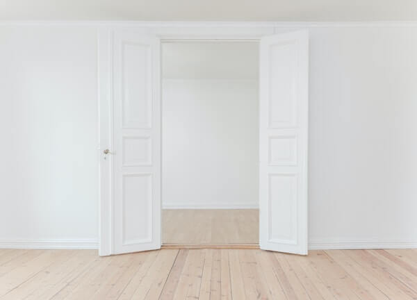 empty white room with light wooden flooring
