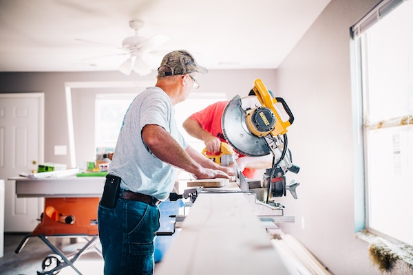 man standing in front of a miter saw