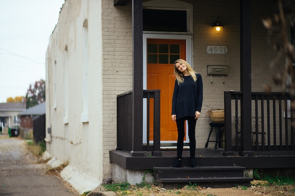 Blond woman standing in front of white brick home.