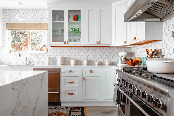 Kitchen with white cabinets and a large gas range.