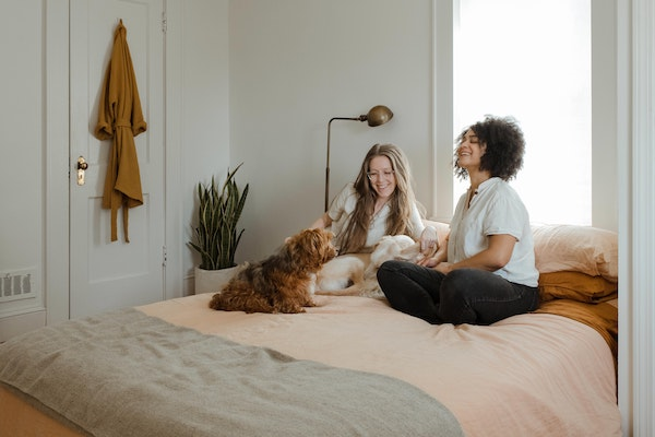 two women sitting on bed with a dog