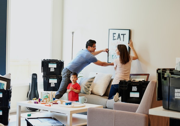 Family hanging a picture in the living room.